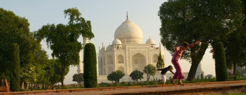 des enfants dansent devant un monument en Inde